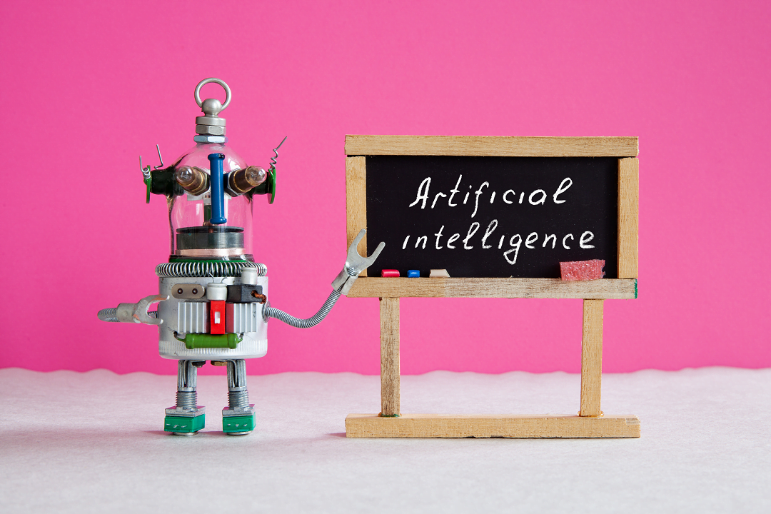 A robot teacher points at an old-fashioned blackboard on which the words 'artificial intelligence' are written
